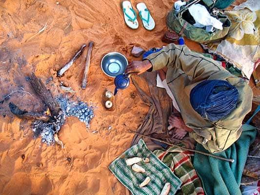 Tuareg tribesman pouring tea in the Sahara desert. Mauritania, West Africa