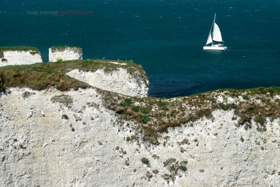 Yacht sailing past Old Harry Rocks in Dorset, England, UK