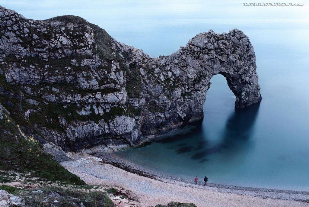 Two people look towards Durdle Door, Dorset, England, UK