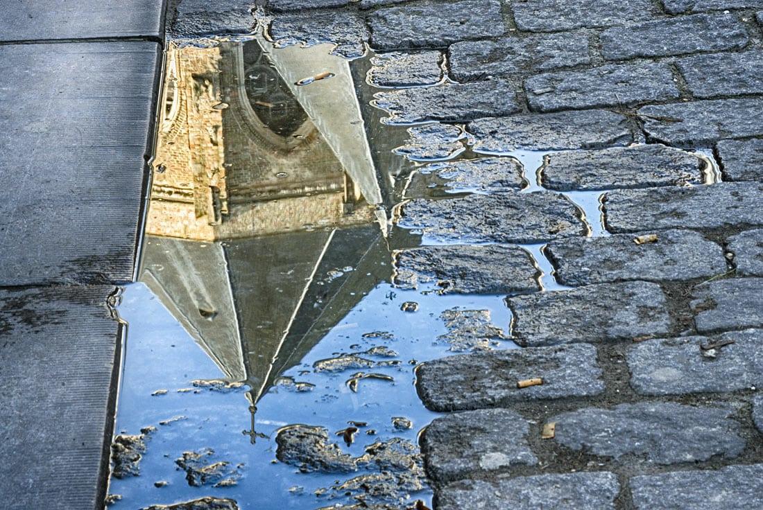 Reflection on a cobbled street, Bruges, Belgium