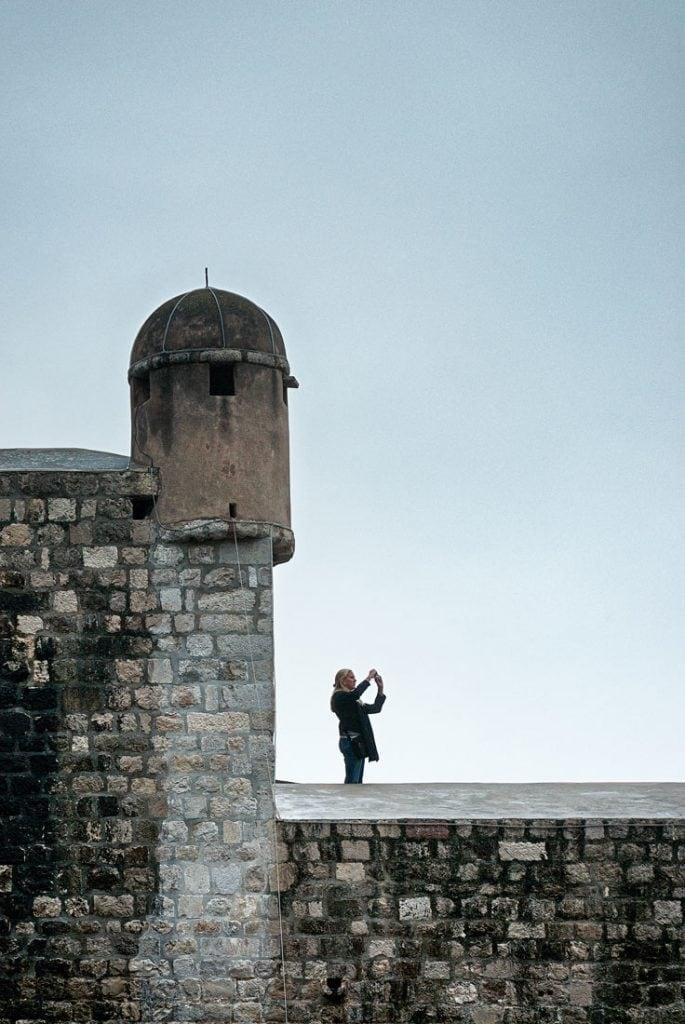 Tourist taking a photo on the city walls of Dubrovnik, Croatia