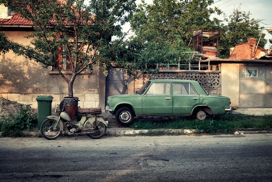 Old car and motorbike in a street in the town of Ivanovo, Romania
