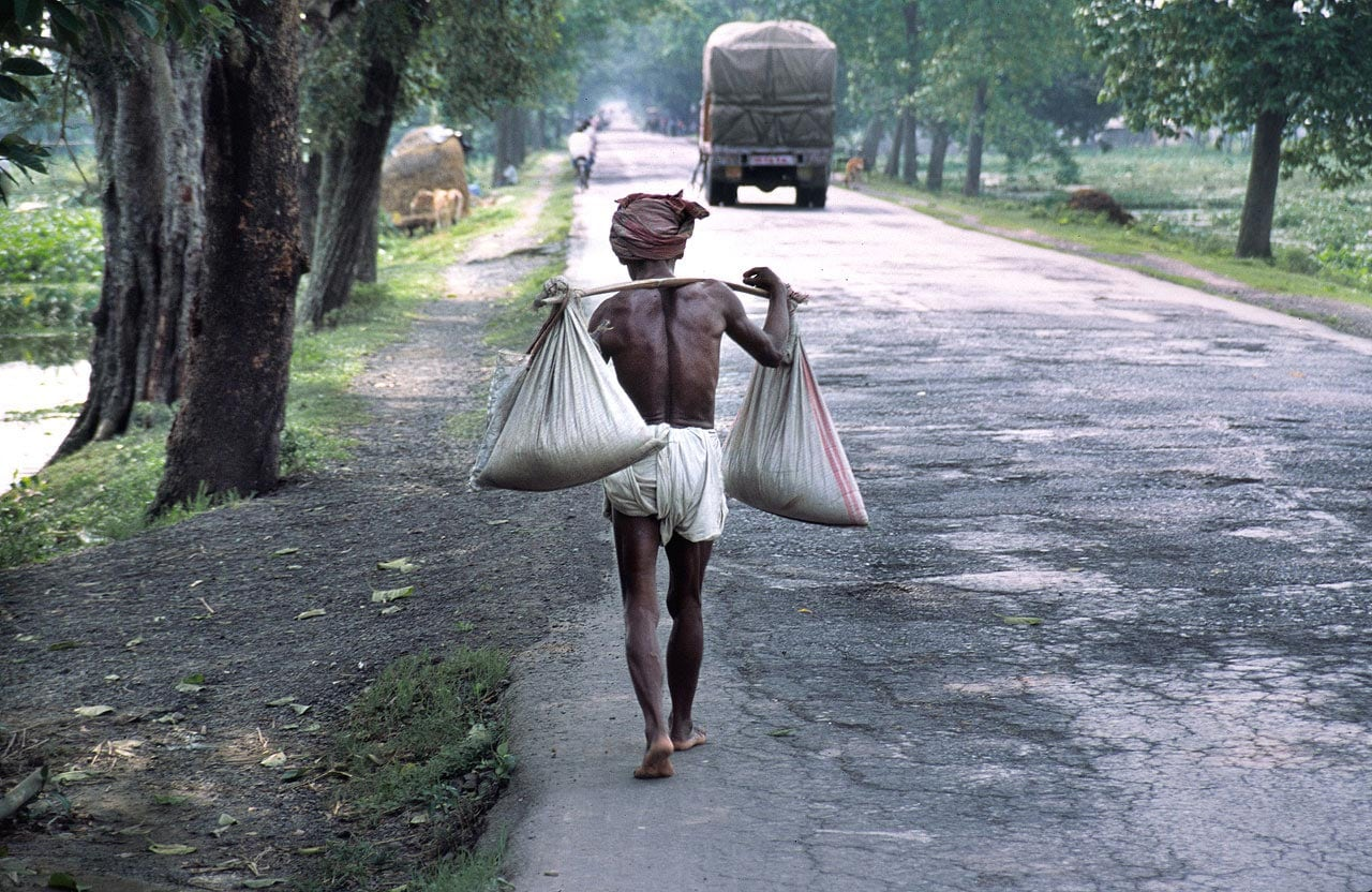 A man carrying goods on a main road in West Bengal, India