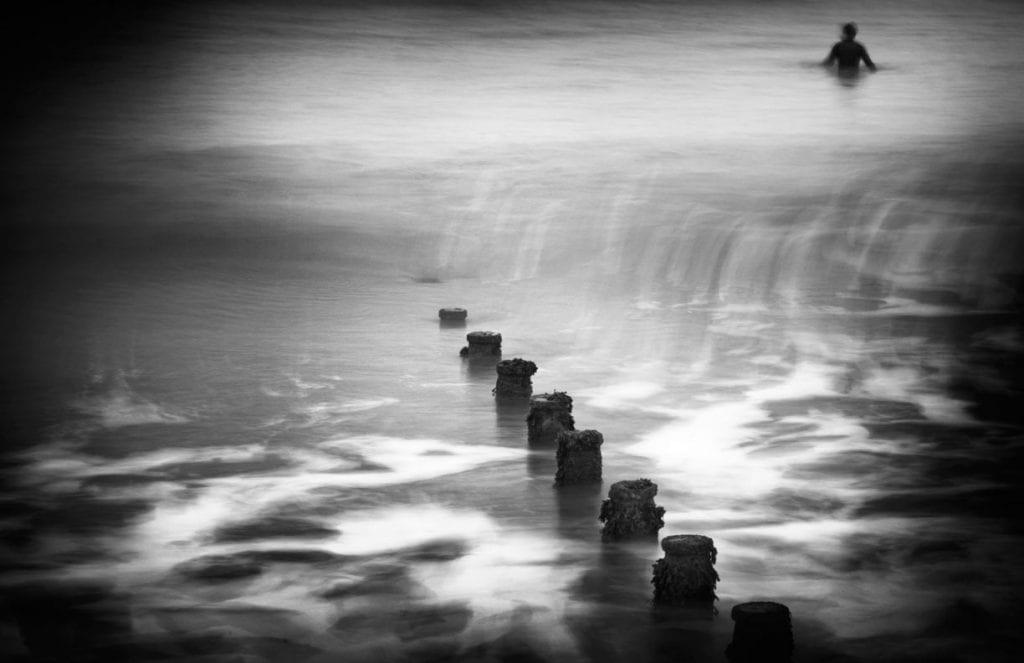 Surfer waits for waves at Bracklesham Bay, West Sussex, England, UK