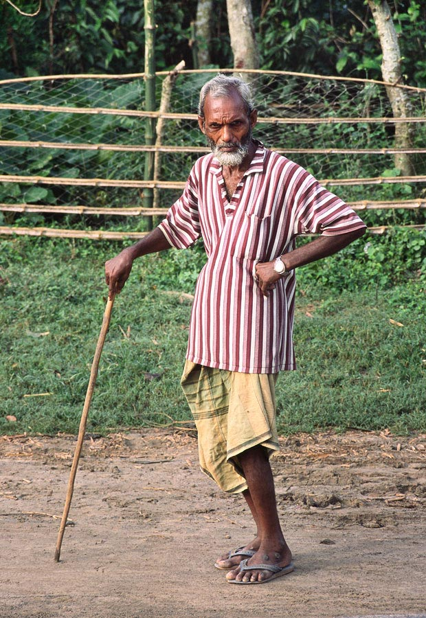Curious, elderly man stops and poses for the camera, West Bengal, India