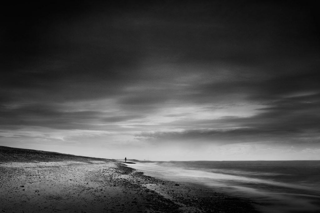 Black and white photograph of a beach scene under dark skies.  Lone figure looking out to sea. Kessingland, UK
