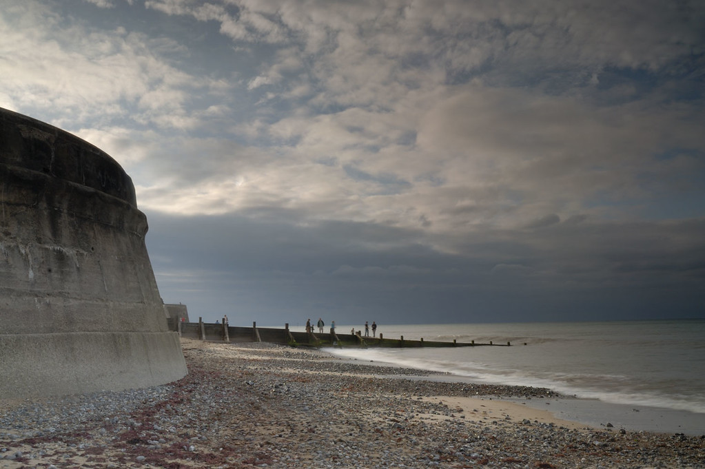 Example of a photo before any post processing is applied. Sea wall and people on the beach at Cromer, Norfolk, England.