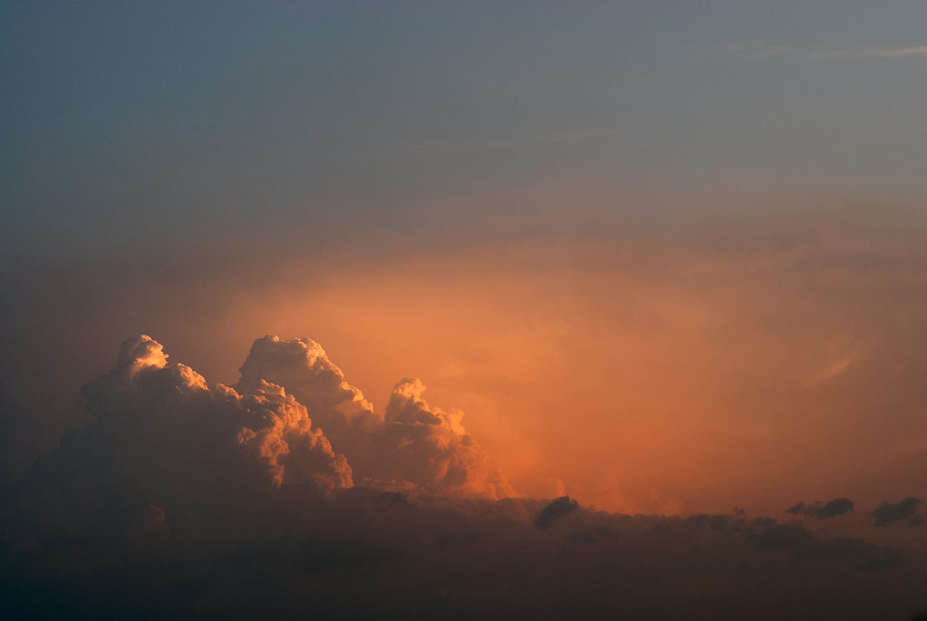 Example of a photograph before any post processing has been applied. Cloud formation at dawn flodded with warm dawn sunlight.