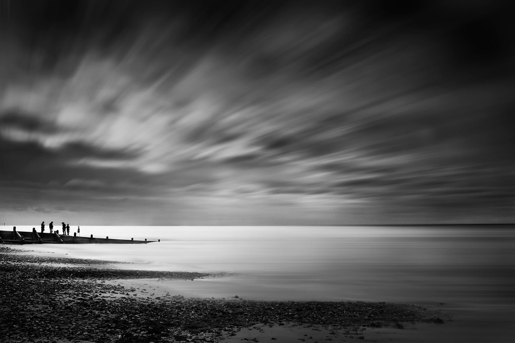 Black and white conversion of an image taken in Norfolk of people playing on the beach. The motion blur in the clouds and sea has been created in Photoshop
